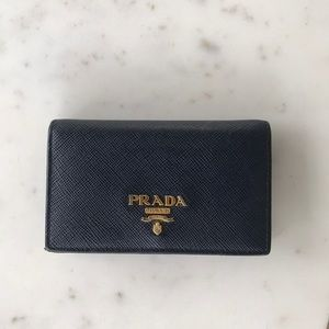 Navy blue Prada accordion wallet with gold detail.